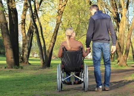 woman in a wheelchair with a man holding her hand